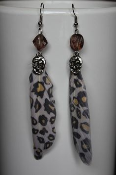 Earrings with panther print feather, a skull pendant and a transparent plastic bead.. €7,95, via Etsy.