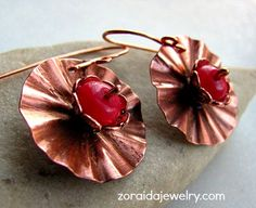 These lovely flower earrings are dimensional in design.  They are made up of layers, a copper disk which was cut and forged by hand and a scalloped bead cap.  The center bead is a red Jade rondelle th