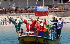 Ruben Torres, dressed in a Santa Claus outfit, and fishermen wave to people from a boat on Christmas Eve along the coast of Valparaiso City, about 75 miles (121 km) northwest of Santiago. (REUTERS)