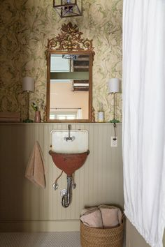 A gilded mirror and ornate wallpaper offer a stark contrast to the salvaged vintage sink, a nod to the apartment's two past lives: an extravagant mansion and servants' quarters. NEXT: Turning a Grain Silo Into a Cozy House