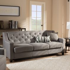 Blending classic button detailing with beautiful fabric upholstery and contrasting wooden legs, this 3-seater sofa from Baxton Studio is expertly crafted from solid hardwood. The sofa provides comfort