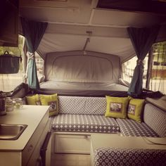 My pop up camper revamp. Cabinets painted white, valance removed, cushions recovered, table tops painted with chalkboard paint, and family photo pillows made with fabric paper. We are loving it!