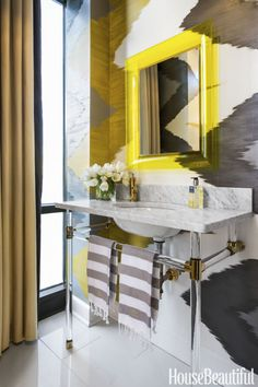 Since there's no need to stash everyday necessities under a powder room sink, the vanity is liberated from its storage task and becomes strictly a statement piece. The Lucite-framed mirror in this powder room is a zingy yellow and continues the theme of transparency. Click through for more powder room decorating ideas.