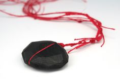 "Julia Turner ""Black Split"" necklace, 2010. Ebony, string. 2 x 1.5 x .5 in (5.1 x 3.8 x 1.3 cm)."