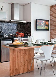 Pastilhas de vidro (Vidrotil) protegem a parede atrás da pia de respingos. O armário suspenso com portas de vidro espelhado é da Formaplas. Cadeiras Série 7 (Ottagono) fazem conjunto com a mesa de teca criada por Piva.