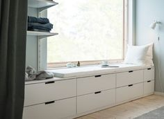 A wall with a window and a row of low bedroom storage made from modern, white chests of drawers