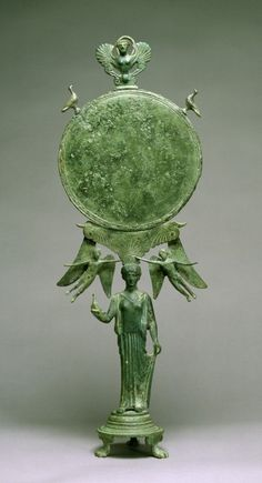 """Caryatid Mirror with Aphrodite  Greek c. 460 BC  A graceful female figure serves as a """"caryatid,"""" or human support, for a mirror. The figure's pose, demure gestures, and simple drapery characterize the quiet elegance of the Early Classical style. The presence of the winged Eros figures (representing the god of love) above suggests that the maiden is a bride or perhaps Aphrodite herself. The siren at the top of the disk recalls the irresistible allure of these mythical bird-women."""