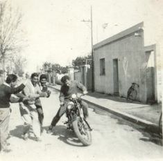 Old photograph of a guy learning to ride a motorcycle.  Don't know if his buddies are encouraging him, or laughing at his efforts.