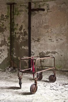 Pictured a gurney with restraints inside an empty asylum