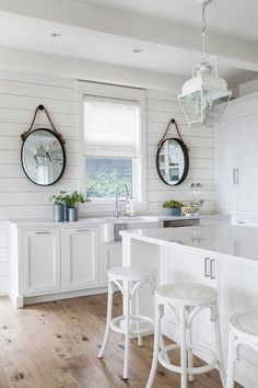 Black rope mirrors hang from a shiplap wall on either side of a kitchen window dressed in a white roman shade positioned above a farmhouse sink with a polished nickel gooseneck faucet mounted to a white quartz countertop accenting white shaker cabinets. Backsplash For White Cabinets, White Shaker Cabinets, White Kitchen Cabinets, Kitchen White, Shiplap In Kitchen, Stairs Kitchen, Kitchen Backsplash, Kitchen Countertops, White Cottage Kitchens