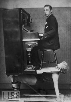 A circus strongwoman balances a piano and a pianist on her chest, circa 1920. I love how unconcerned he looks.