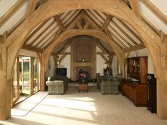 An arch collar brace frame creates a traditional look to the sitting room along with the revealed rafters above. Timber Roof, Timber Buildings, Timber Frame Homes, Timber House, Timber Frames, Viking House, Oak Frame House, Rustic Home Design, Interesting Buildings