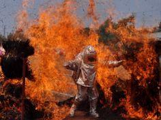 Bombeiro passa por uma parede de chamas durante a Semana de Segurança contra Incêndios de Bhubaneswar, leste da Índia. Foto: Asit Kumar/AFP