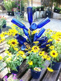 Bottle tree stands make it super simple to create garden art with favourite bottles. Pick your favourite colours of glass and go for it. #spon