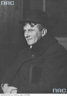 Karol Stryjeński - architekt, artysta rzeźbiarz. Fotografia sytuacyjna. W płaszczu i kapeluszu.