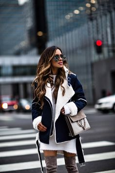 fashion blogger mia mia mine wearing a white sweater dress and j.o.a. denim biker jacket from asos