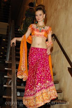 Model displays an orange and pink lehnga at Shehnaai's Bridal Fashion Showcase