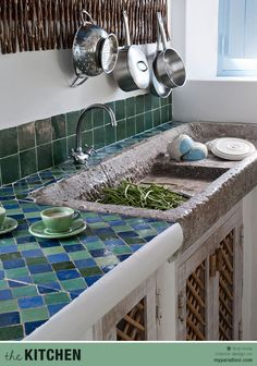 An ethnic kitchen with stone sink and colored tiles by Vera Iachia.