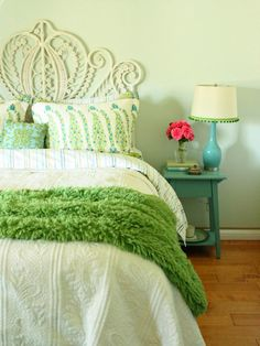 A bright green bedroom features an ornate metal headboard on a bed covered by a matelasse bedspread. A wooden nightstand provides the perfect place for a vase of flowers.