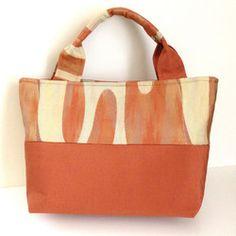 鮮やかなオレンジ色の帯をリメイクしたバッグです。裏生地は、赤色の生地を使用しています。内側ポケットつき。マグネットボタンつき。中敷つき。*サイズ(アバウト寸) タテ:26㎝ ヨコ:40㎝ マチ:10㎝ モチテハバ:4㎝ モチテナガサ:42㎝