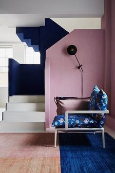 Staircase in navy blue, white and pink accent walls in the same space.
