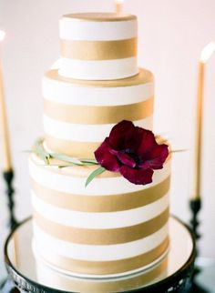 Gold Stripe Wedding Cake Surrounded by Candles   Sarah Beth Photography   http://heyweddinglady.com/moody-glam-winter-wedding-burgundy-blush-black/