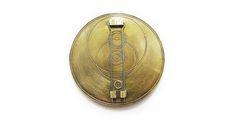 Åsa Christensson. Brooch: Solarian, 2012. Brass, zinc, glass, mahogany veneer. 9 x 0.5 x 9 cm. Photo by: Åsa Christensson. From series: Beyond. Back view.