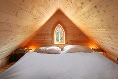 The Loft with stained glass arch window in the Tiny Tumbleweed house, so compact but so comfy
