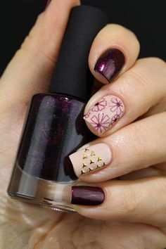Combining nude and violet polish painted with fall flower details and gold beads added on top.