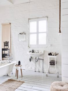 modern bathroom with vintage decor, white painted brick walls and wood floors and freestanding white tub. / sfgirlbybay