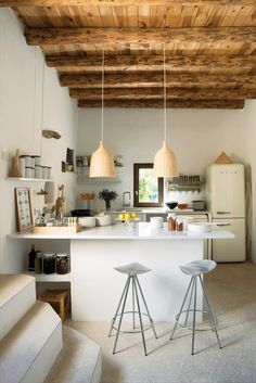 Jamaica barstools by Pepe Cortès for Knoll and two Ikea pendants pair nicely with the plaster walls, restored wooden beam ceilings, and polished cement floors in the kitchen.