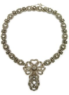 Antique diamond pendant necklace by Cartier, Paris c.1905, of 18th century style, centred by an openwork ribbon tied bow with similar drop, each with principal brilliant cut diamond to the middle in beaded collet mount, on a row of lozenge shaped cluster links joined by ribbon bows, all set throughout with rose cut diamonds, close set in silver and gold, numbered. #Cartier #antique #necklace
