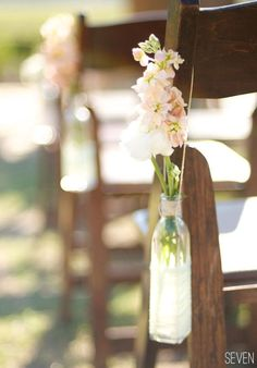 Close up of how to hang....    {ceremony} Use flowers and recycled bottles as aisle markers. Tie to chairs or sit them on the ground close by. Can use a cheaper flower or fillers such as babys breath - use mason jars