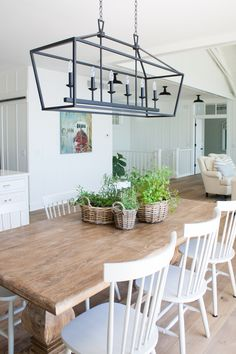 Lake house dining room with wide plank oak flooring, white board and batten walls and rustic table and grey dining chairs.
