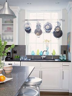 Keep pots and pans convenient with a hanging pot rack. Here a stainless-steel rack -- just above the sink -- allows the homeowner to wash pots and pans and hang them up to dry in the same spot.