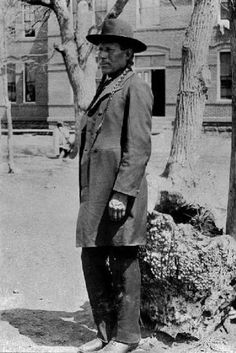 Watan (the husband of Crawling Wolf and Big Face), standing in front of the girl's dormitory at the Seger Indian Training School in Colony, Oklahoma - Southern Arapaho - before his death in 1932: