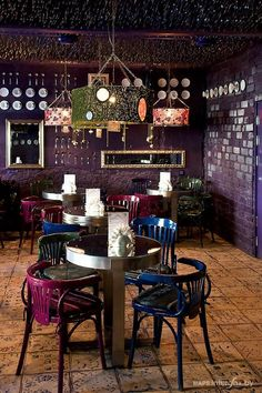 Cafe - The Forgotten Garden. I love the dark purple brick walls and the mismatched chairs and lampshades.