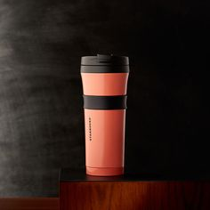 A double-walled, stainless steel tumbler with a grippy center band and shiny coral finish.