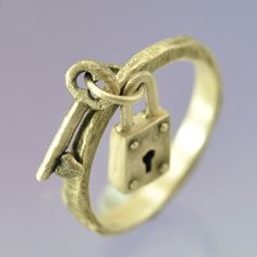 Padlock and Key    Sterling silver ring featuring handmade charms of a padlock and key.    The key has a small heart on it and both are attached to