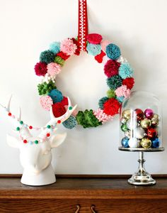 Use pom poms and craft garland to make this colorful wreath.