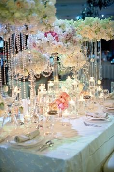 This wedding tablescape is a favourite. Pastel flowers, crystal, candlelight and crisp white linen and dinnerware. Elegant !