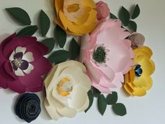 Paper flowers wall decor by Mi Prima Belle. A gorgeous addition to your baby girl's nursery room or big girl's bedroom. They can spruce up your guest room, dining room and living room and entryway! So many uses! Gorgeous as a wedding flower backdrop, too! Yellow, light pink, purple, cream and plum paper flowers with a touch of navy blue and vintage gold accents.