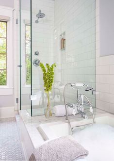 The designer picked English-style chrome faucets—not nickel, because she finds that nickel-finish coordinates and accessories can be expensive. Hidalgo-Nilsson extended the marble slab tub platform into the shower to serve as a seat. Pinned with chrome brackets, a clear vertical sheet of frameless tempered glass lands on the platform to divide the areas.