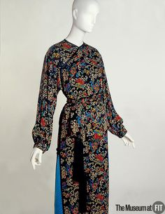 Yves Saint Laurent. Black silk crepe and turquoise damask dress. 1977- 1978 France. An evening ensemble consisting of trouser suit with theatrical extravagance and prints of chinese influence. Museum at FIT New York.