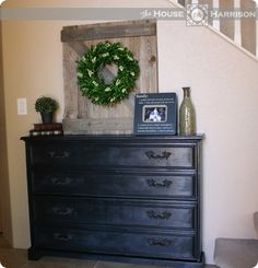 Cute barndoor wreath holder, black chest of drawers to hold coats, books, bags, scarves, gloves, or even board games