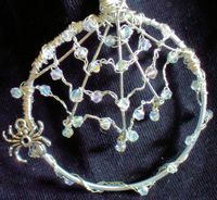 """Wire Work, Jewelled Spider's Web ((Supply list and brief instructions.)) ... TIME: 2hrs 30min Difficulty: Tricky. Posted by BeckyP., Birmingham, England .. .. """"This was tricky to make, the hardest part was getting the main supporting wires placed and fixed to the bangle,the rest was so so,the braiding and adding the crystals was easy, just wraping the wire around the suporting wires of the web, but having the patience paid off."""" Hang it in a window for a sparkling effect."""