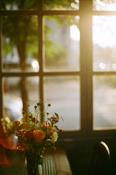 a vase of flowers and a window to look out of