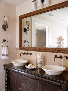 Traditional Home with Southern Charm, His and Hers: Dual basins rest atop a traditional cabinet in the master bathroom. The large mirror is an antique. Emphasizing the importance of proper lighting, the Coxes installed overhead lamps and side sconces to enhance the quality of light in the room.