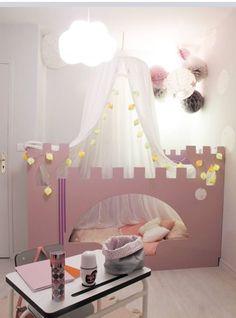 Pour une chambre enfant de princesse le lit a été transformé en mini château rose comme un lit cabane et un ciel de lit descend du plafond.
