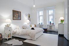 White bedroom with dark floors